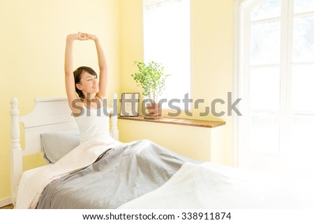 attractive asian woman in the bedroom - stock photo