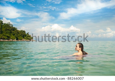 Attractive Asian Woman in the Ocean swimming in the ocean - stock photo