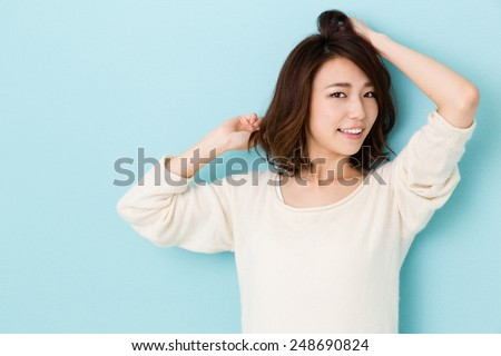 attractive asian woman isolated on blue background - stock photo