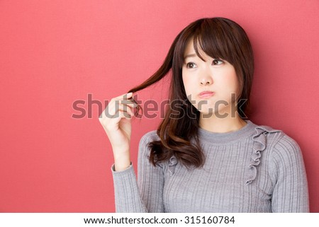 attractive asian woman isolated on red background - stock photo