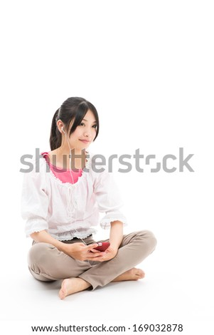 attractive asian woman listening music on white background