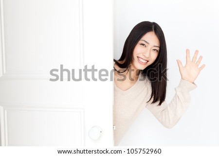 attractive asian woman opening door - stock photo