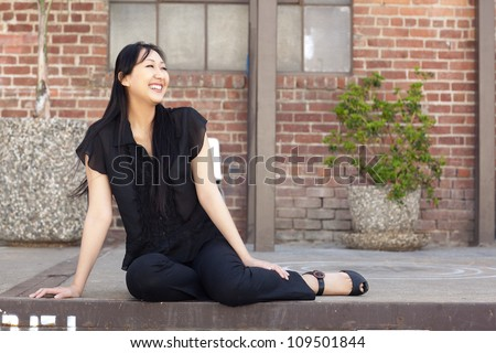 Attractive Asian woman outdoors wearing short sleeved black shirt and black pants - stock photo