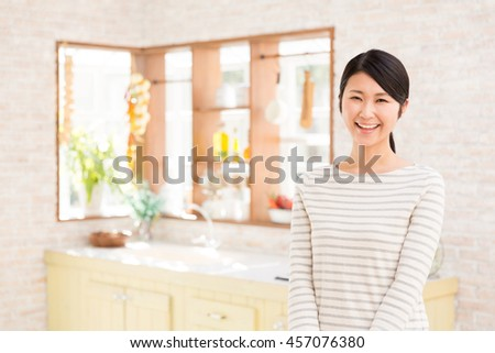 attractive asian woman relaxing in a kitchen