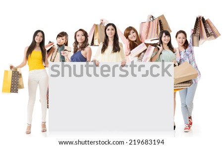 Attractive Asian woman shopping and one lady holding blank board, full length portrait isolated on white background. - stock photo