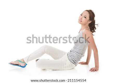 Attractive asian woman sit on ground. Full length portrait isolated on the white background.