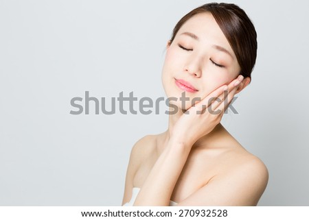 attractive asian woman skin care image on gray background  - stock photo