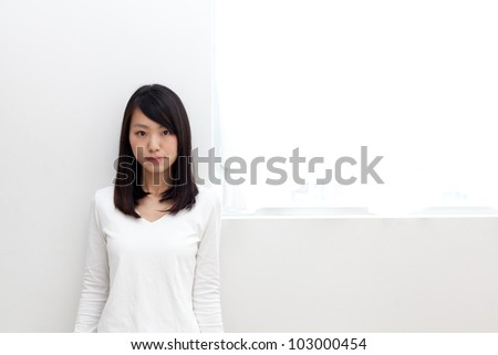 attractive asian woman standing beside of window - stock photo