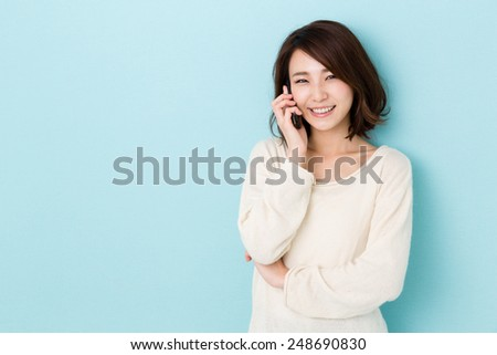 attractive asian woman talking isolated on blue background