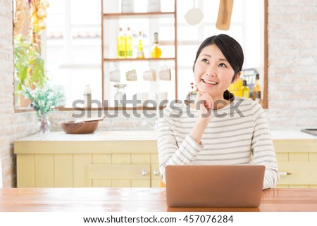 attractive asian woman using laptop in a kitchen