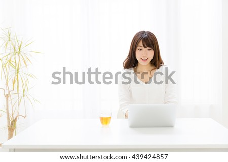 attractive asian woman using laptop in the living room