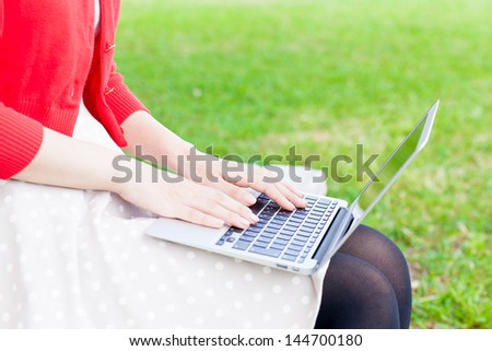 attractive asian woman  using laptop in the park - stock photo