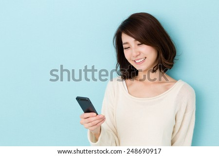 attractive asian woman using smart phone isolated on blue background