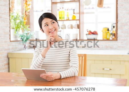 attractive asian woman using tablet computer in a kitchen