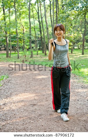 attractive asian woman walking in the park