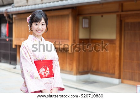 attractive asian woman wearing kimono walking on old street