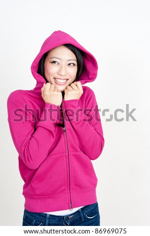 attractive asian woman wearing pink parka - stock photo