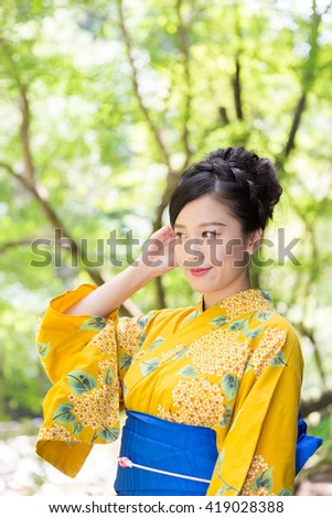 "attractive Asian woman wearing traditional Japanese casual summer kimono called ""Yukata""."
