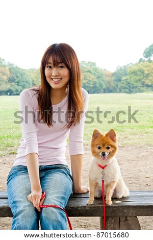 attractive asian woman with dog in the park - stock photo