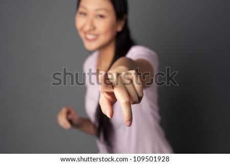Attractive Asian woman with long black hair shot against a studio background. - stock photo
