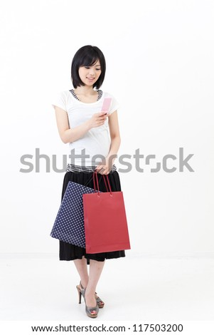 attractive asian woman with shopping bag on white background - stock photo
