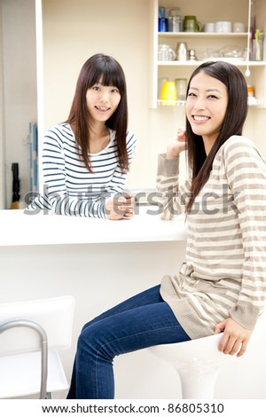 attractive asian women relaxing in the kitchen - stock photo