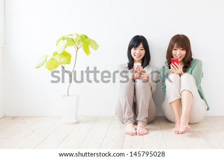 attractive asian women using smart phone in the room - stock photo