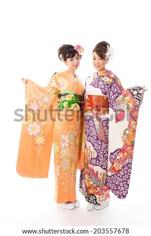 attractive asian women wearing traditional kimono on white background - stock photo