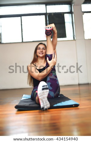 Attractive athlete young woman doing exercise. Indoors.  - stock photo