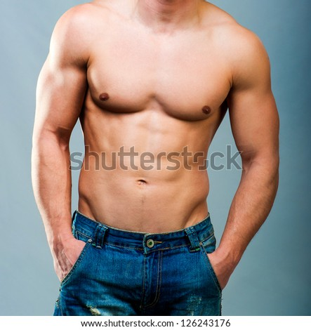 attractive athletic male torso on a gray background
