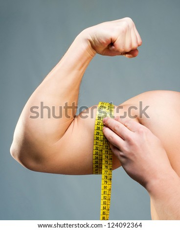 attractive athletic man measuring his hand - stock photo