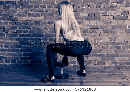 Attractive athletic woman in black leggins performing deadlift with dumbbell at the gym, view from the back - stock photo