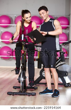 Attractive athletic young woman working out with a fitness instructor or personal trainer in the gym on an exercise bicycle - stock photo