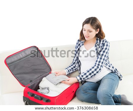 Attractive awaiting woman packing children's clothes into bag in order to go to maternity home. - stock photo