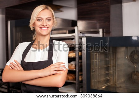 Attractive baker is standing near special equipment and smiling. The woman crossed her hands. She is looking at the camera with joy. Copy space in right side - stock photo