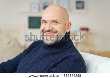 Attractive bald middle-aged man with a goatee sitting relaxing on a couch at home looking at the camera with a lovely wide engaging smile - stock photo