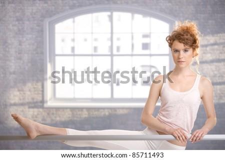 Attractive ballerina girl practicing by bar in dance studio front of window.? - stock photo