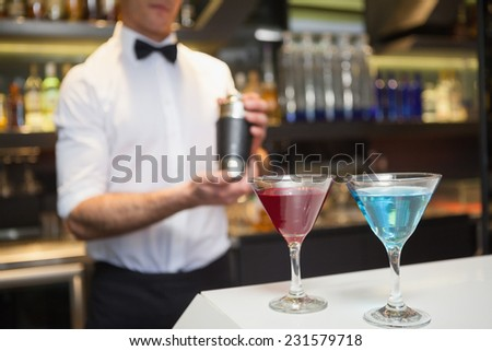 Attractive bar man making a cocktail in a bar - stock photo