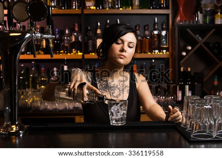 Attractive bartender pouring a drink - stock photo