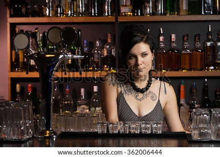 Attractive bartender with drinks - stock photo