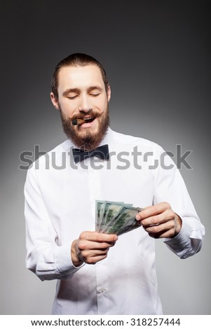 Attractive beard man is holding money in his hands. He is standing and smiling. The man is smoking a cigar. Isolated on black background - stock photo