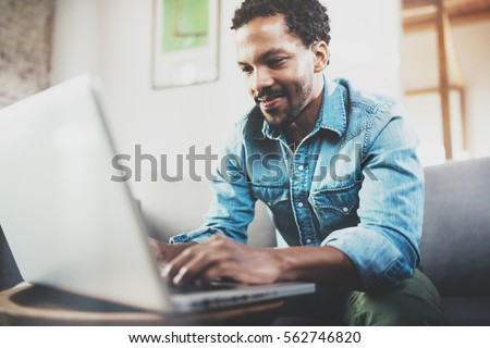 Attractive bearded African man spending free time in sofa and using laptop at modern home.Concept of young people enjoying mobile devices.Blurred background.