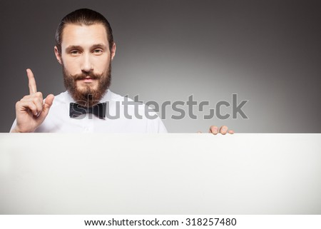Attractive bearded hipster guy is presenting white empty placard. He is standing and pointing finger up with seriousness. Isolated on grey background - stock photo
