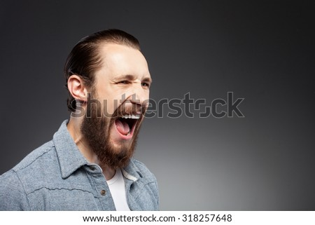 Attractive bearded hipster guy is showing his aggression. He is screaming negatively. The guy is standing and looking aside with irritation. Isolated on black background and copy space in right side - stock photo