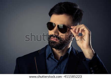 Attractive bearded man in suit touching his glasses