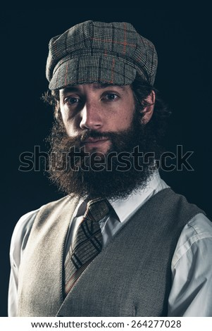 Attractive bearded man in vintage fashion wearing a cloth peaked cap and waistcoat looking at the camera with an enigmatic smile, dark background - stock photo