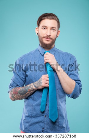 Attractive bearded man is adjusting his tie. He is standing and looking at camera with joy. The man is smiling. Isolated on blue background - stock photo