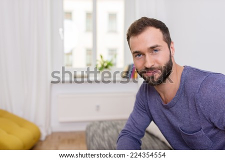 Attractive bearded man with a friendly smile sitting on a sofa in his apartment looking at the camera - stock photo