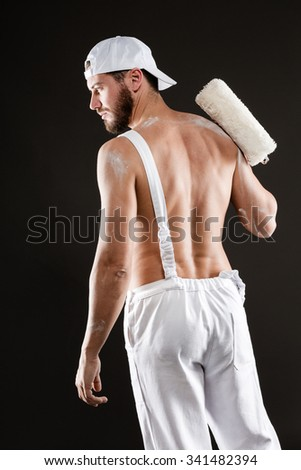 Attractive bearded young painter in white dungarees, hat and bare chest standing back with paint roller, on a gray background - stock photo