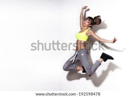 Attractive beautiful brunette woman jumping in studio. - stock photo